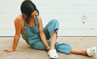 Woman posing in overalls, sunglasses, and Classic Clogs in white.