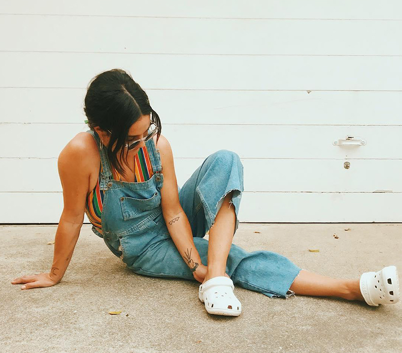 Woman wearing overalls, sunglasses, and Classic Clogs in white.
