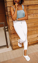 Woman posing in white jeans, a camisole, and Classic Clogs in white.
